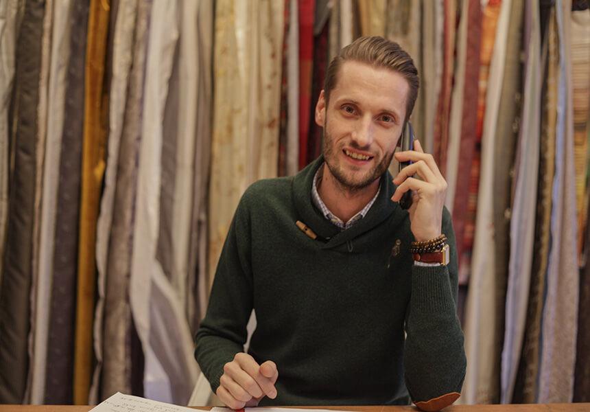 Raumausstatter Adler Wohndesign in Berlin, Kreativchef Norman Drewitz, Beratung mit Kunden Kontaktam Telefon,