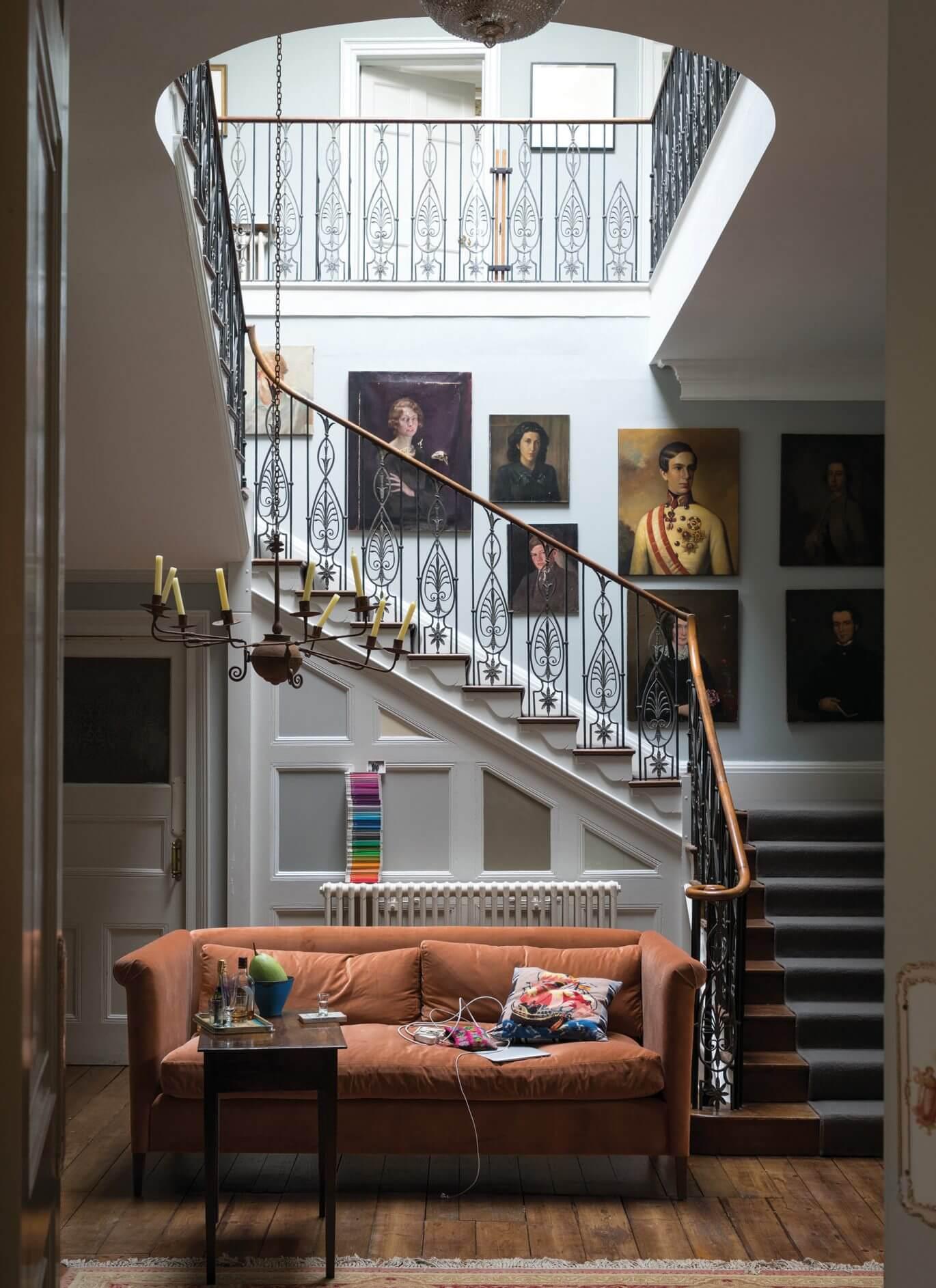 Treppenhaus Wandgestaltung mit Blackened in Kombination mit dem wärmeren Wimborne White und einer einfallsreichen Gestaltung der Paneele hinter dem Sofa.