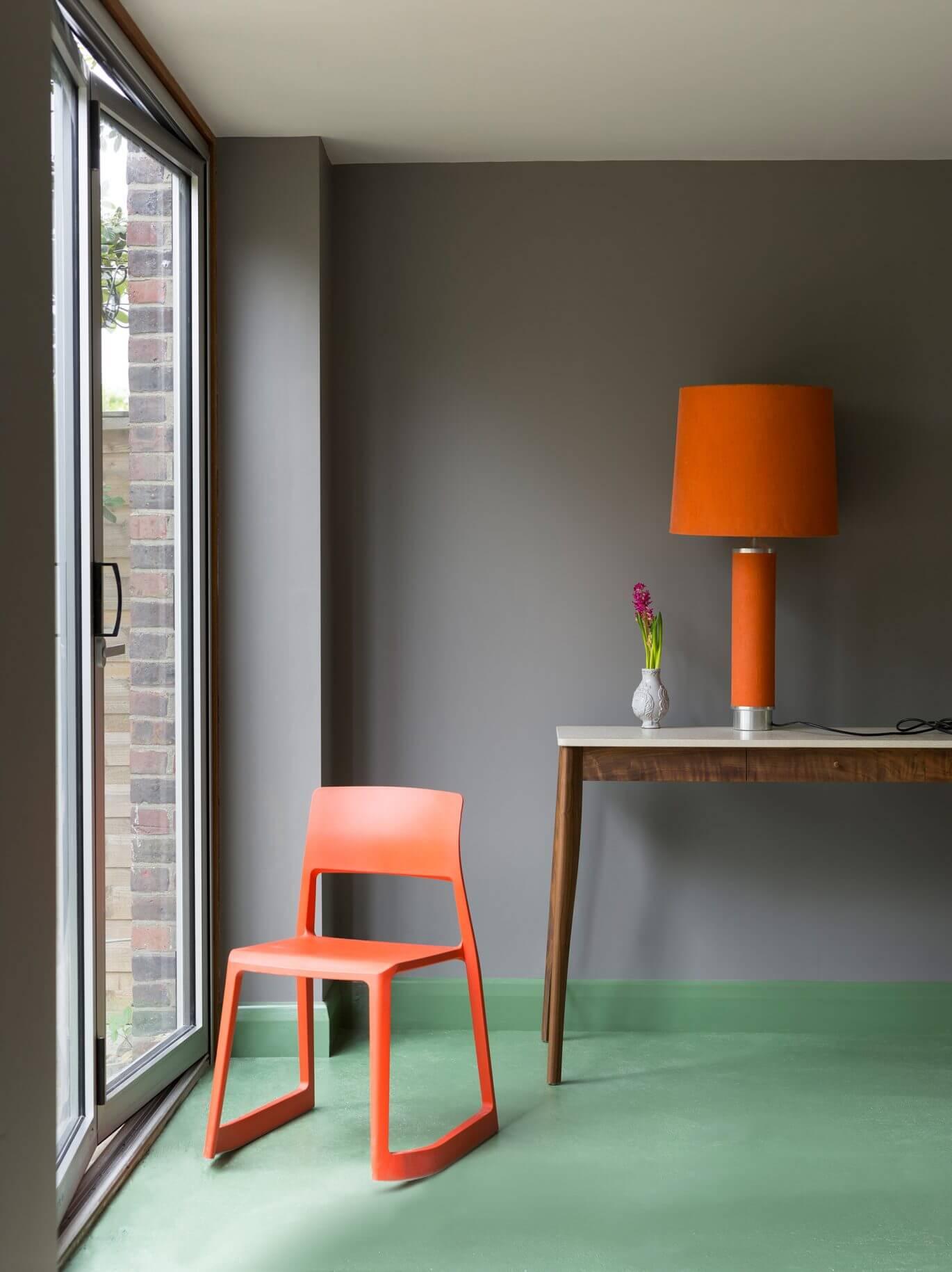 Wohnzimmer mit einer Glastür, einem grünen Boden, einem orangefarbenen Stuhl und Wänden im Farbton Mole's Breath.