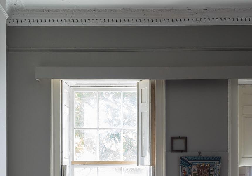 Die quer über dem Fenster verlaufende Gardinenblende wurde mit Dead Flat in der Farbe Worsted lackiert.