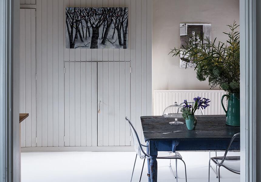 Blick vom Flur in das Wohnzimmer und ein mit Estate Eggeshell lackierter Schrank mit Holzlamellen