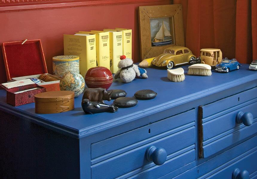 Estate Eggshell im Farbton Drawing Room Blue auf einer Kommode vor einer roten mit Modern Eggshell gestrichenen Wand