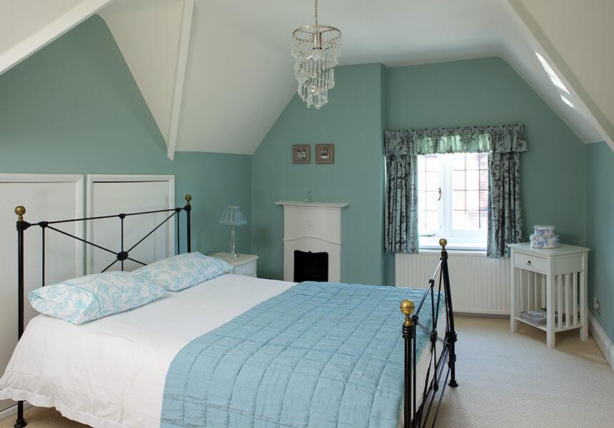 Die englische Farbe Estate Emulsion in Green Blue im Schlafzimmer mit einer passenden Tagesdecke