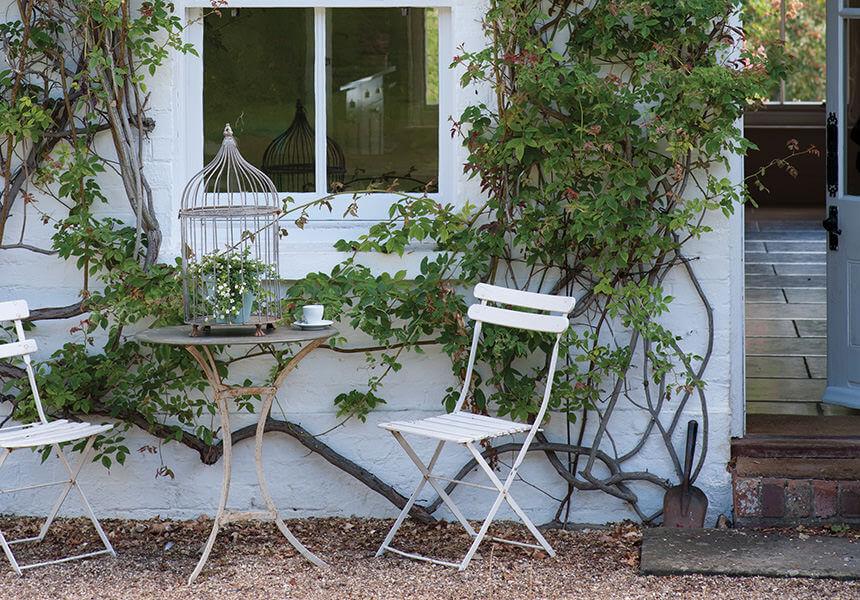 Diese Fassade ist mit Kletterpflanzen bewachsen und mit Exterior Masonry weiss gestrichen. Vor der Fassade stehen zwei Gartenstühle und ein Tisch.