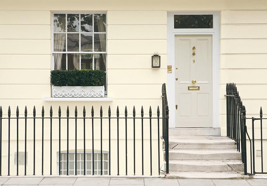 Cremefarbener Hauseingang mit einem dunklen Zaun. Exterior Masonry als helle Fassadenfarbe.