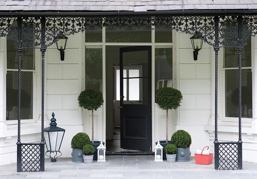 Hauseingang mit zwei Buchsbäumen und einer in weiß in Exterior Masonry gestrichenen Fassade mit einer Varanda