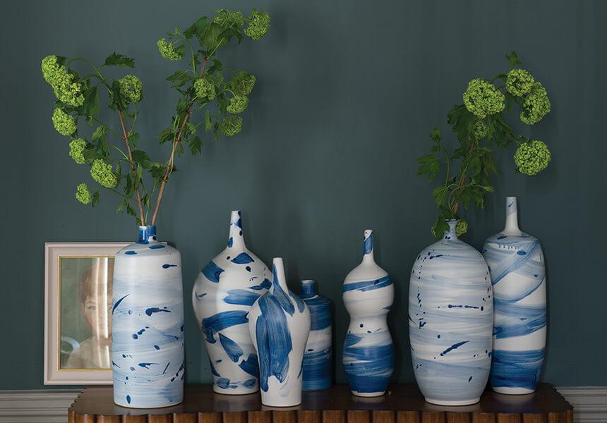 Hier wurde Casein Distemper Vasen in der Farbe Inchyra Blue als Wandgestaltung eingesetzt. Vor der Wand steht ein Tisch mit Vasen.